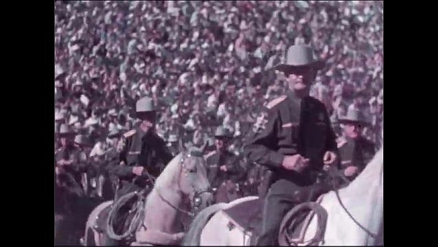 1940s: Two officers ride on horses in parade in stadium, carrying flags, with officers on horses behind them.