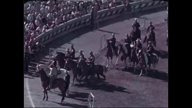 1940s: Police officers ride on horses in formation around stadium for parade. Officers ride horses through gate leading out of stadium.