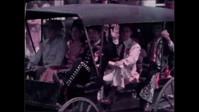 1940s: Man in fancy police uniform rides horse down road, raising hand to crowd lining street. People in costumes ride in buggy down street for parade.