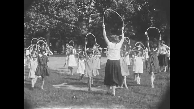 1920s: NEWARK, NEW JERSEY, UNITED STATES: children play on swings at Branch Brook Park. Girls with hoops. Children on merry go round in park.