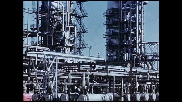 1950s: UNITED STATES: towers and tanks at oil refinery. Crude oil refinery. Pipeline at refinery. Pipe still.