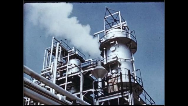 1950s: UNITED STATES: solvent extraction plant. Pipes at refinery. Treatment towers. Solvent flows through pipes. Man monitors process.