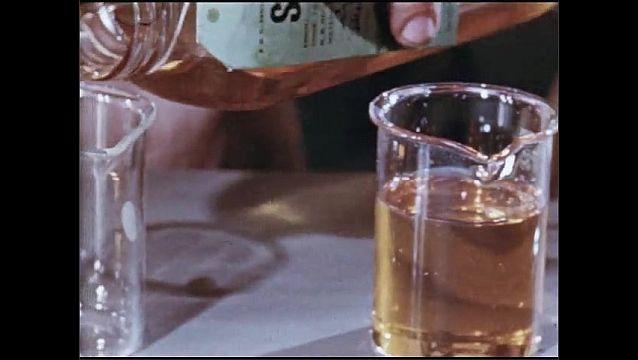 1950s: UNITED STATES: viscose oil. Man blends oils in glass beaker.