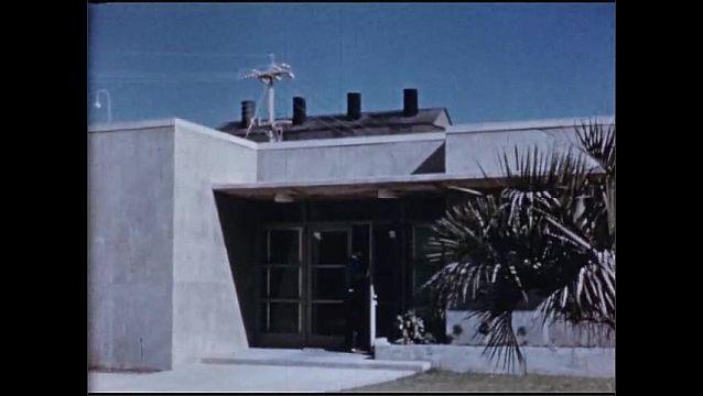 1950s: UNITED STATES: Esso Lubrication Engineer visits plant. Men enter building. Man runs plant. Men shake hands at desk. Men in meeting.