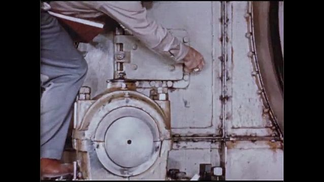 1950s: UNITED STATES: jack shaft drives drill. Gear shield lubricant for machine. Man climbs down ladder from machine