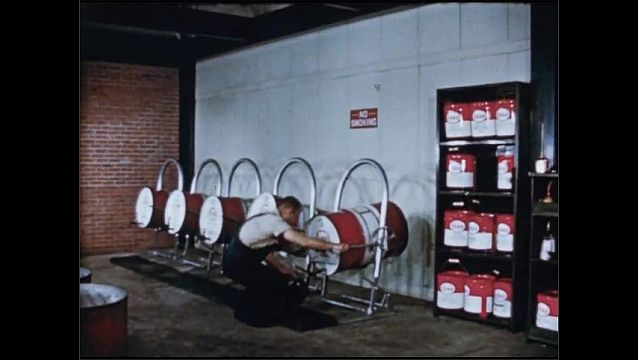 1950s: UNITED STATES: man puts notes on wall. Man checks lubricant storage. Man opens drum. No Smoking sign.