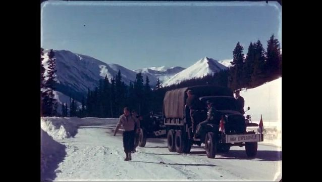 1940s: Men in military truck pull howitzer down snowy mountain road. Men ride on and walk beside military truck.
