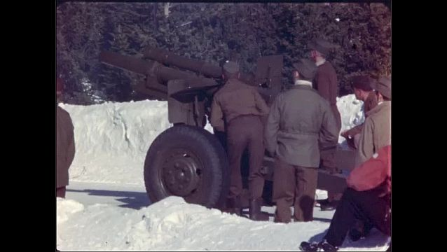 1940s: Soldiers wave and fire howitzer gun. Shell explodes and snow flies from side of snowy mountain.