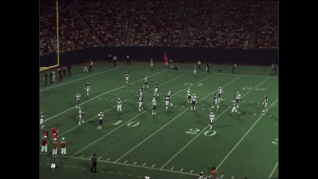 1970s:  Football field. Teams at the 8 yard line. Quarterback throws the ball beyond the end zone, no one catches it. Teams at the 20 yard line, play ends in a small pile.