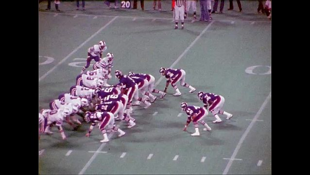1970s: Football Field. 2 football plays, both are hand-offs into tackles and pile-ups.