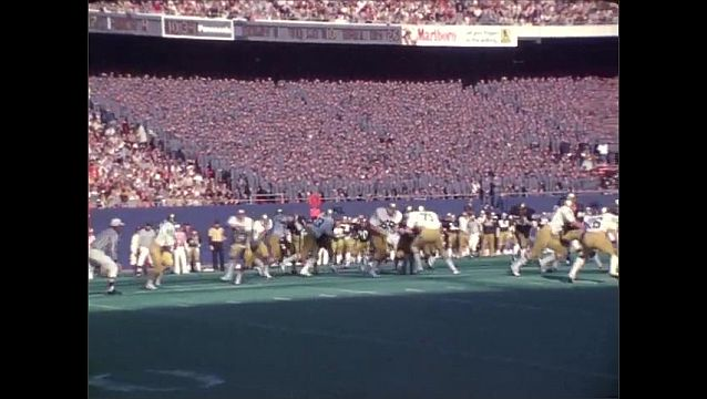 1970s: Football field. Two football plays. Runs and tackles. News cameraman films on the sidelines.