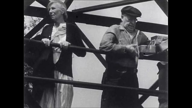 1950s: Man and woman stand at bridge railing, man opens toolbox, throws tools into water, throws toolbox into water. Man and woman walk away. Children stand at bottom of bridge, stare at water.