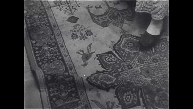 1950s: Old woman sits up in bed, straightens out rug, removes vacuum from cabinet.