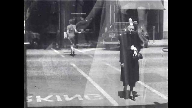 1950s: Woman looks at herself in mirror. Woman walks down street, crosses street.