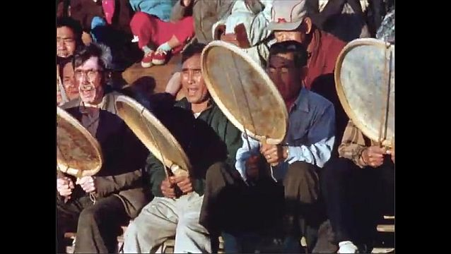 1970s: Man dances. Men sit and drum. People watch.