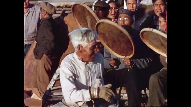 1970s: Man dances. Men sit and drum. People watch. Women dance.