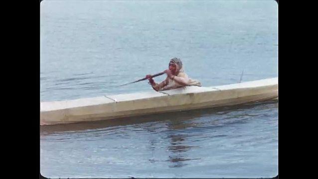 1970s: Man sits in kayak in ocean, rocks kayak back and forth, flips kayak upside down, rights kayak. Man stands up to show waterproofing on kayak.