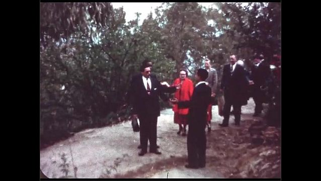 1940s: Man greets group of people walking down path together and joins them on their walk.