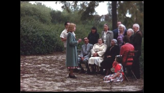1940s: Woman stands before group of people seated in chairs in park, talking to them. Seated man talks.