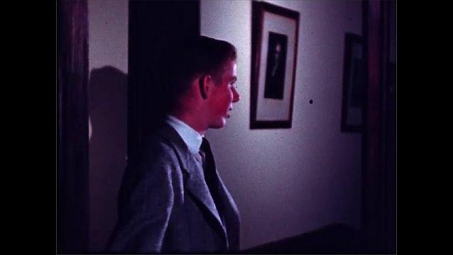 1950s: Man in suit sits at desk and speaks. Boy in doorway smiles and shuts door.