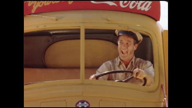 1950s: The Coca-Cola truck driver happily drives and smiles. The driver whistles and waves out the window.