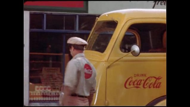 1950s: The Coca-Cola truck stops at Maudsleys 16th Street Market and the driver gets out. Two sharply-dressed women walk down the sidewalk and the driver bumps into them, carrying cases of Coca-Cola.
