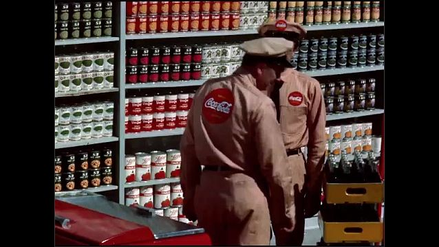 1950s: Two  Coca-Cola deliverymen talk in a grocery store under a poster for Coke. The deliverymen speak and turn to the Coke cooler.