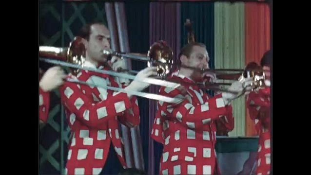 1940s: Band playing on stage. Trombone players stand. Band playing, saxophonist playing in front.