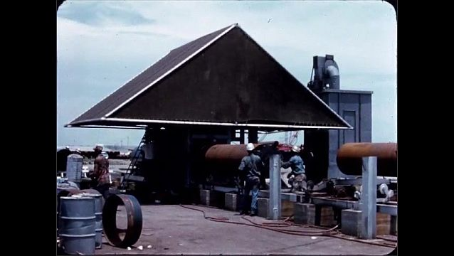 1940s: UNITED STATES: men lift reels onto rollers. Pipe on rollers. Men move pipes into position