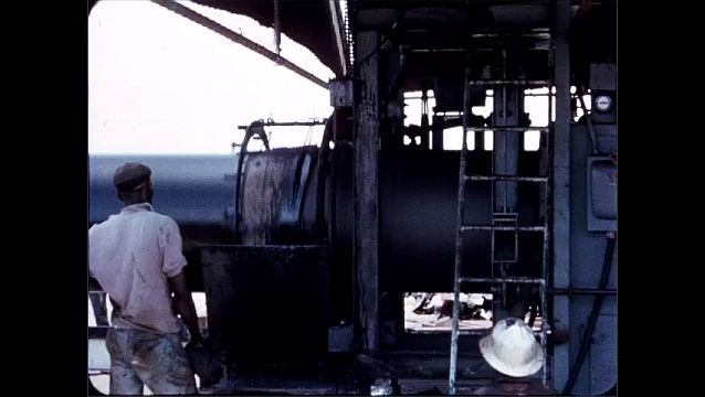 1940s: UNITED STATES: machine coats pipes. Man removes reel from machine.