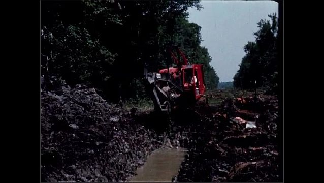 1940s: UNITED STATES: machinery clears ditch through forest. Water in ditch. Digger moves mud from trench.