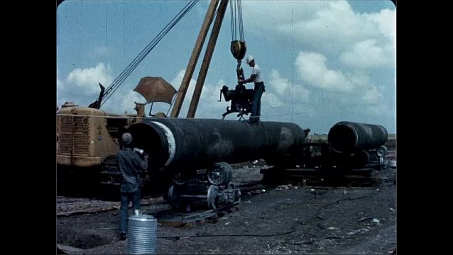 1940s: UNITED STATES: man stands on top of pipe being moved by crane. Man guides machinery. Man turns handle on crane.