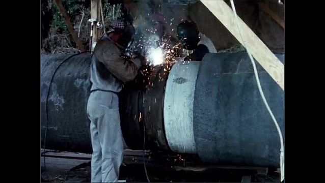 1940s: UNITED STATES: man welds end of pipes together. Men connect pipe section to pipeline. Sparks from welding