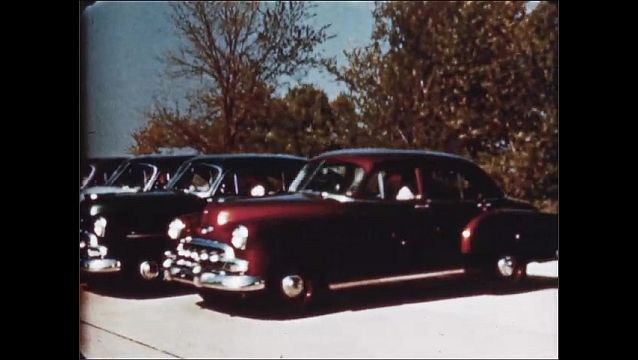 1940s: Backwards tracking shot, cars pull up and park in succession.