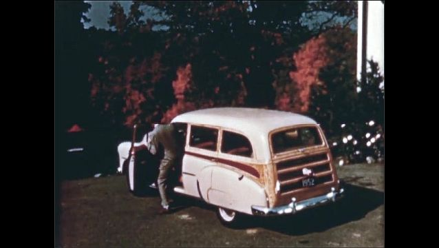 1940s: People get into car. Rear view of car with trunk open. View of suitcases in trunk.