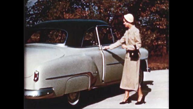 1940s: Woman walks to car, opens car door, zoom in on car.