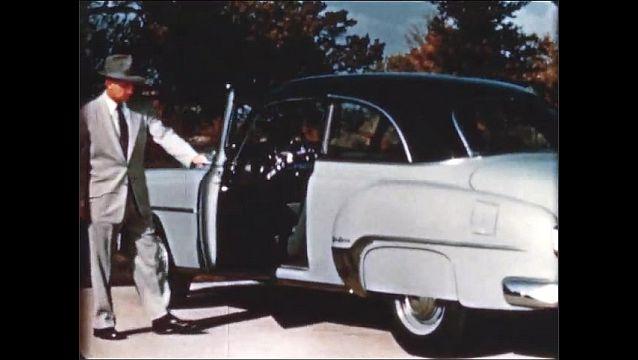1940s: Man walks to car, opens car door, zoom in on car.