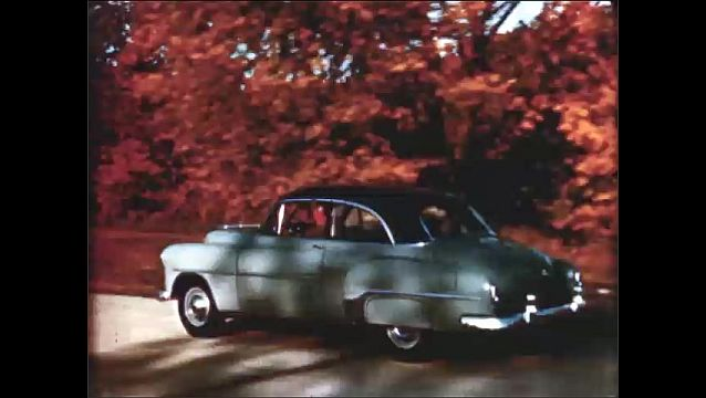 1940s: High angle, women in car, car pulls away. Tracking shot of car driving, dissolve to different car color.