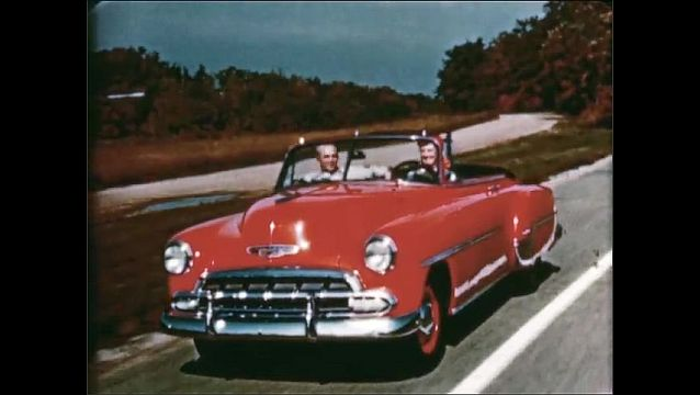 1940s: Tracking shot of car driving. Couple driving on road. High angle of car. Overhead shot of car.