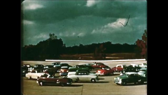 1940s: High angle, cars driving on street. Cars circling in formation. Cars pass camera. Cars driving around turn.