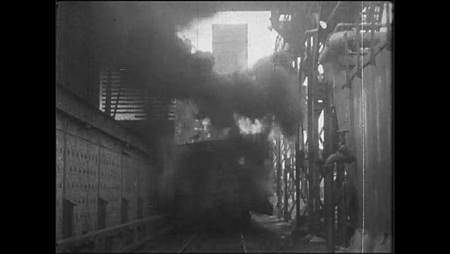 1920s: Factory.  Smokestacks.  Men work with molten metal in furnace.