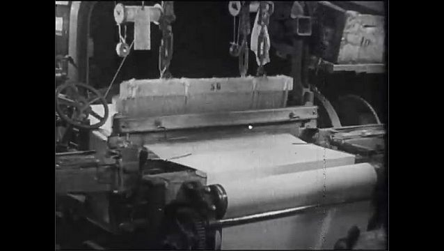 1920s: Men load bales of cotton onto ship.  Machines fill spools of thread and cut fabric.  Crane moves load.  Ship leaves port.