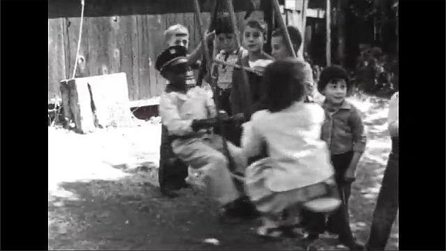 1940s: Children play on playground with bowls. Children swing on swing. Children sleep in beds.