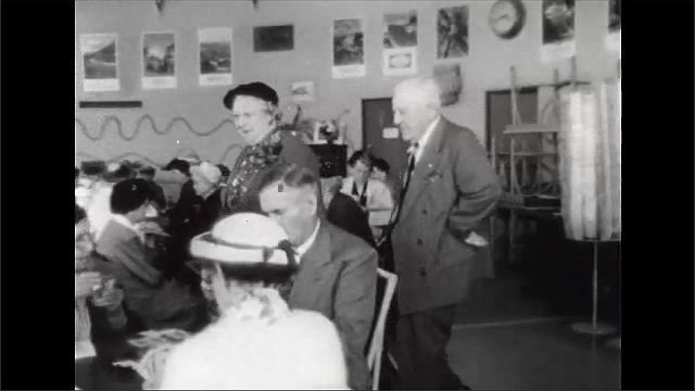 1940s: Woman welcomes man and woman into senior center. Man and woman walk through room, shake hands with people seated at tables.