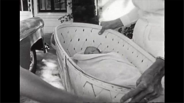 1940s: Old people play shuffleboard. Woman watches. Man pushes puck, smiles. Nurse picks up basket with baby inside, carries basket to door. Nurse lays baby down in crib.