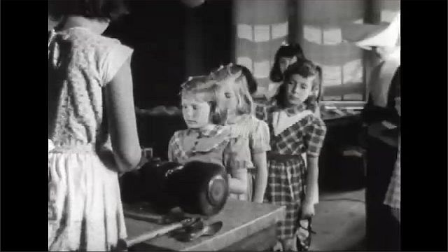 1940s: Man and boy stand next to woman holding baby. Nun escorts children into line. Woman helps girl shine shoes.