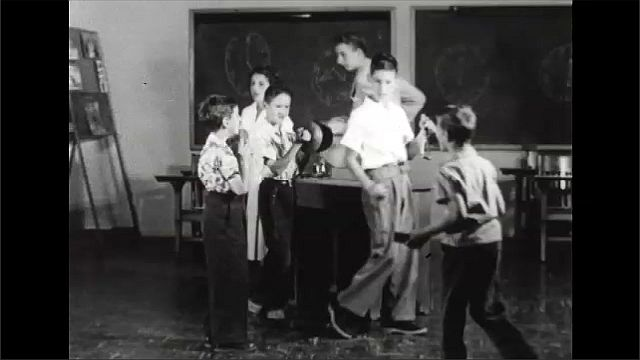 1940s: Children parade around room, play instruments. Woman sits in chair next to child.