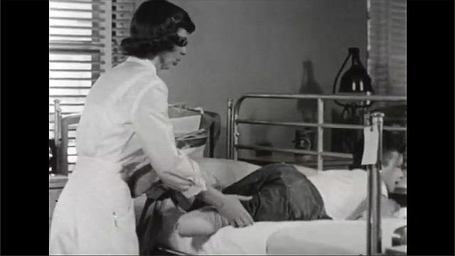 1940s: Boy sits in hospital bed, touches armpit, talks. Nurse feels boy's chest, helps boy roll over and slide out of bed. Nurse hands boy crutches.