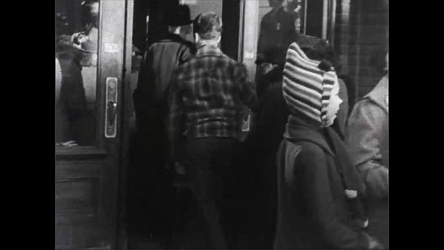 1940s: Pedestrians on sidewalk in town. People enter store. Man exits store with package. Man and woman on street corner with packages.