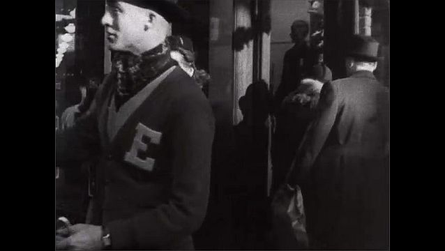 1940s: Pedestrians on sidewalk in town. Couple look in store window.